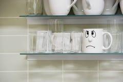 Taza triste de la cara en estante Fotografía de archivo libre de regalías
