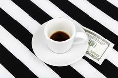 Taza vacía con cientos dólares como extremidad en un blanco y negro Imagen de archivo libre de regalías