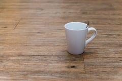 Taza vacía del café con leche en la tabla de madera Fotografía de archivo