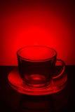 Taza vacía transparente de cristal de té y platillo en un fondo rojo Imagen de archivo libre de regalías
