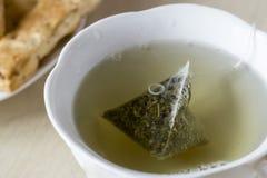 Taza verde del brebaje de las bolsitas de té Fotos de archivo libres de regalías