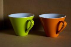 Taza verde y anaranjada Imagen de archivo libre de regalías