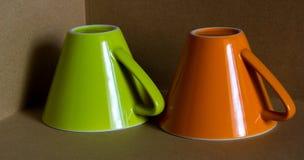 Taza verde y anaranjada Imagenes de archivo