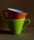 Taza verde y anaranjada Foto de archivo libre de regalías