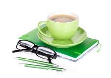 Taza, vidrios y materiales de oficina verdes de café Foto de archivo