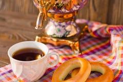 Taza y buñuelo de té del samovar en una servilleta en una jaula Imagen de archivo