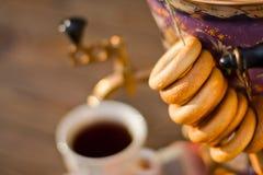 Taza y buñuelo de té del samovar en una servilleta en una jaula Foto de archivo libre de regalías