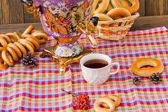 Taza y buñuelo de té del samovar en una servilleta en una jaula Fotografía de archivo libre de regalías