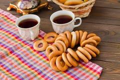 Taza y buñuelo de té del samovar en una servilleta en una jaula Imágenes de archivo libres de regalías