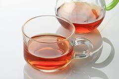 Taza y caldera de té en el fondo reflexivo blanco Fotos de archivo libres de regalías