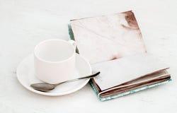 Taza y cuaderno blancos del vintage en una sobremesa de madera blanca Foto de archivo libre de regalías