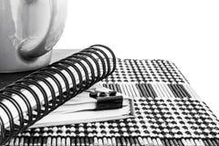 Taza y cuaderno calientes de café en la estera de madera, foto blanco y negro Foto de archivo libre de regalías