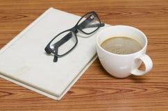 Taza y cuaderno de café con los vidrios Imagenes de archivo