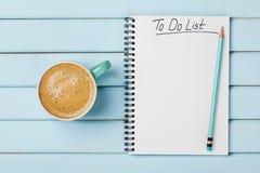 Taza y cuaderno de café con para hacer la lista en el escritorio rústico azul concepto desde arriba, de la planificación y de dis Fotos de archivo