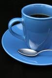 Taza y cuchara de café en negro imagenes de archivo