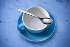 Taza y cuchara vacías de café imagenes de archivo