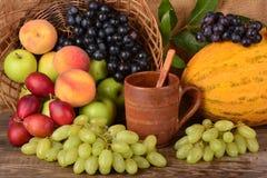 Taza y frutas coloridas, aún vida de la arcilla del viejo alfarero Imagen de archivo