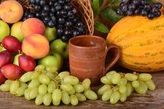 Taza y frutas coloridas, aún vida de la arcilla del viejo alfarero Fotos de archivo libres de regalías