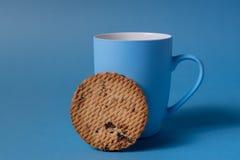 Taza y galleta azules en un fondo azul imagen de archivo