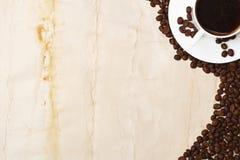 Taza y grano de café en el fondo blanco Imagen de archivo libre de regalías