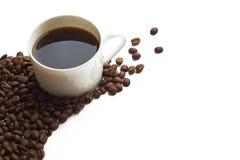 Taza y grano de café en el fondo blanco Fotografía de archivo