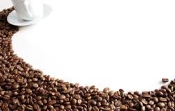 Taza y grano de café en el fondo blanco foto de archivo