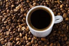 Taza y habas de café Foto de archivo libre de regalías