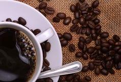 Taza y habas de café Imagenes de archivo