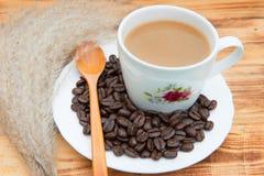 Taza y habas de café imagen de archivo