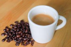 Taza y habas de café Fotos de archivo