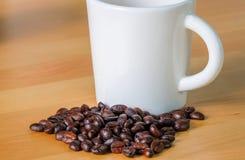 Taza y habas de café Foto de archivo