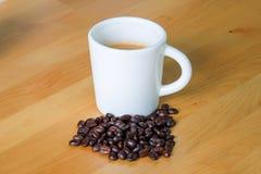 Taza y habas de café Fotos de archivo libres de regalías