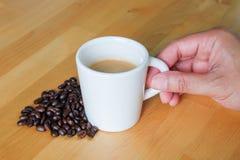 Taza y habas de café del control de la mano Fotos de archivo libres de regalías