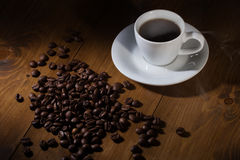 Taza y habas de café en la tabla de madera Imagen de archivo