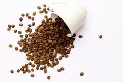 Taza y habas de café en un fondo blanco foto de archivo