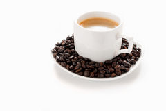 Taza y habas de café en un fondo blanco Foto de archivo libre de regalías