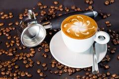 Taza y habas de café en un fondo negro Fotos de archivo
