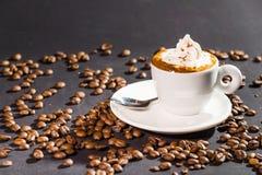 Taza y habas de café en un fondo negro Foto de archivo libre de regalías