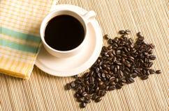 Taza y habas de café en una tabla Fotos de archivo