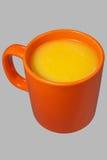 Taza y jugo anaranjados Fotos de archivo