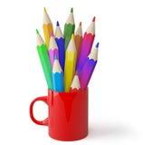 Taza y lápices coloreados. Foto de archivo
