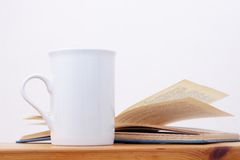 Taza y libro blancos Imágenes de archivo libres de regalías