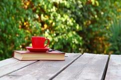 Taza y libro de la taza de café sobre la tabla de madera al aire libre, en el tiempo de la tarde Foco selectivo Fotos de archivo