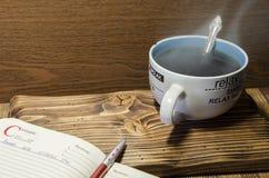 Taza y libro de té Imagenes de archivo