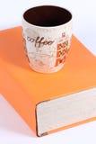 Taza y libro viejo con el fondo blanco imagenes de archivo