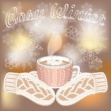 Taza y manos calientes del cacao con las manoplas en fondo borroso con los copos de nieve fotografía de archivo