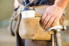 Taza y martillo disponibles de café en el carpintero imagen de archivo libre de regalías