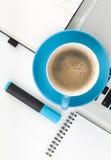Taza y materiales de oficina azules de café Fotos de archivo libres de regalías