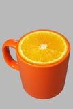 Taza y naranja anaranjadas Foto de archivo libre de regalías