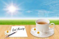 Taza y papel de café con buena mañana de la palabra Foto de archivo libre de regalías